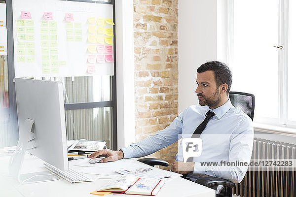 Businessman in office using computer at desk