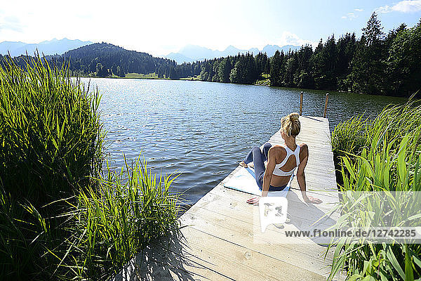 Germany  Mittenwald  back view of woman relaxing on jetty at lake