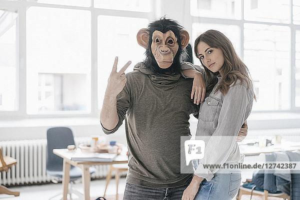Man wearing chimpanzee mask  making victory-sign  woman leaning on him