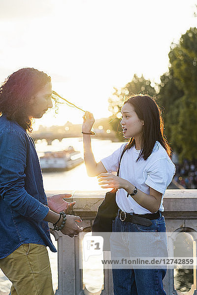 France  Paris  young couple standing on a bridge at river Seine at sunset