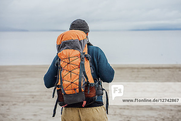 Man with backpack looking at lake  rear view