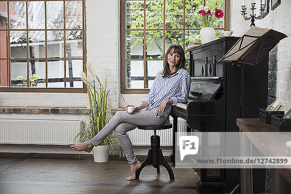 Woman sitting at piano  drinking coffee