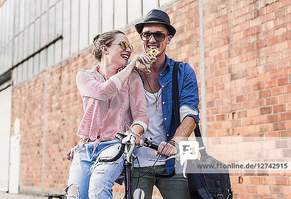 Happy young couple with bicycle sharing a snack