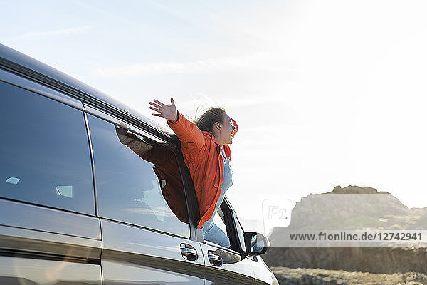 Happy woman leaning out of car window on a road trip
