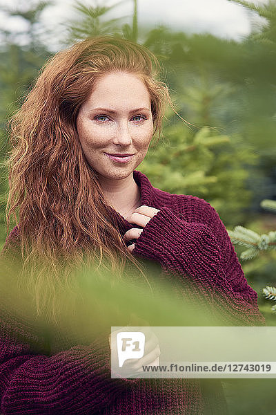 Portrait of smiling redheaded young woman in nature