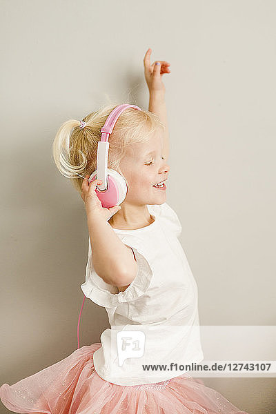 Dancing little girl listening music with headphones