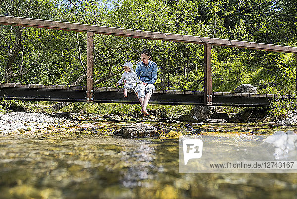 Mother and daughter sitting on wooden bridge  mountain stream