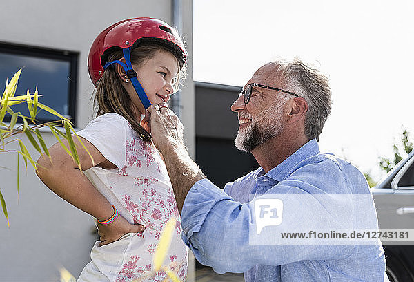 Mature man fixing safety helmet on little girl's head