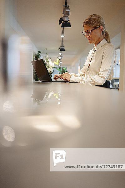 Businesswoman in office using laptop