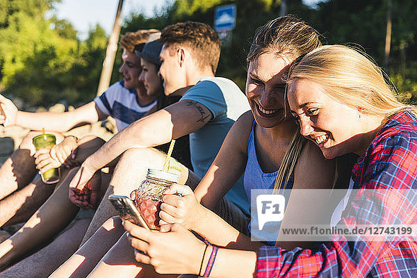 Group of happy friends sitting outdoors with refreshing drinks and cell phones