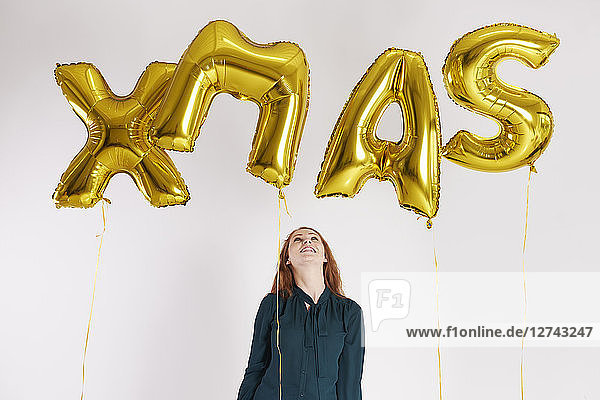 Young woman with golden balloons building the word 'xmas'