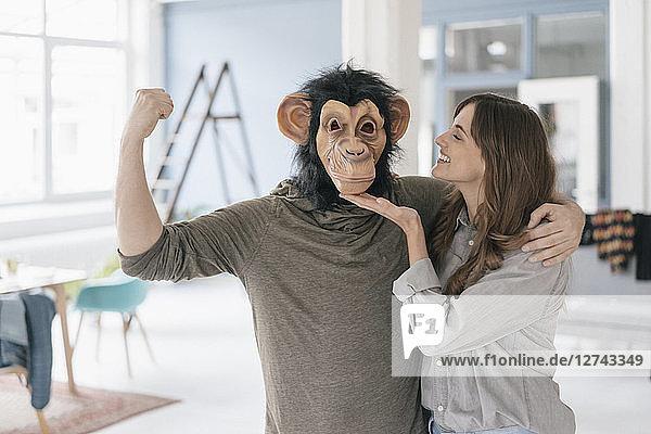 Man wearing chimpanzee mask  flexing muscles  woman petting him