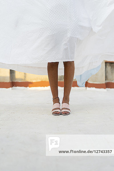Legs of young woman hiding behind drying bed sheet