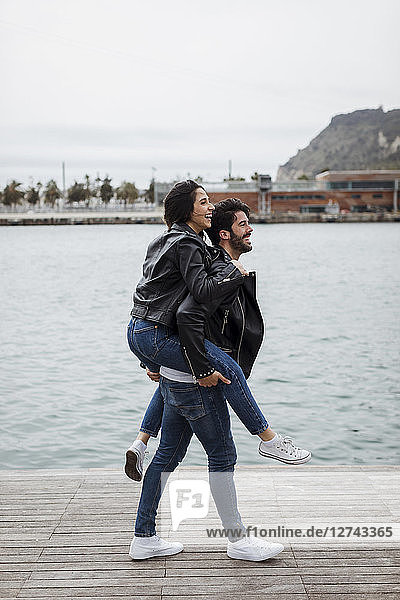 Spain,  Barcelona,  happy young couple having fun at the coast