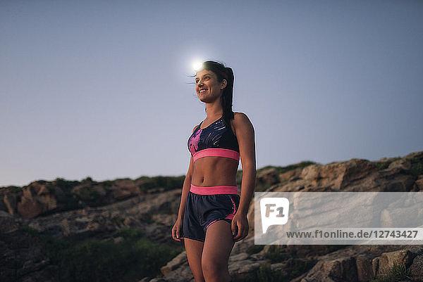 Sportive woman with headlamp standing on rocky coast