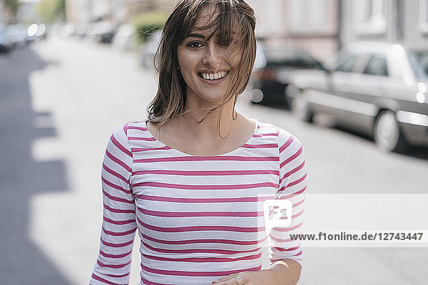 Happy young woman walking in the city