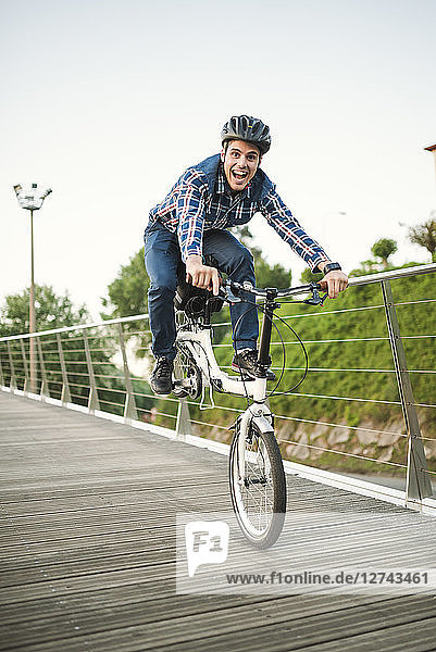 Young man doing tricks with a folding bike