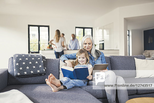 Grandmother and granddaughter sitting on couch  reading together book and tablet pc
