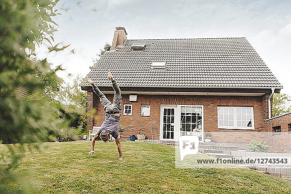 Mature man doing a handstand in garden of his home