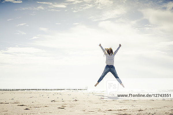 Happy woman having fun at the beach  jumping in the air