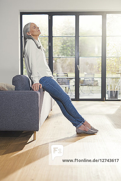 Senior woman standing by couch in living room  with eyes closed