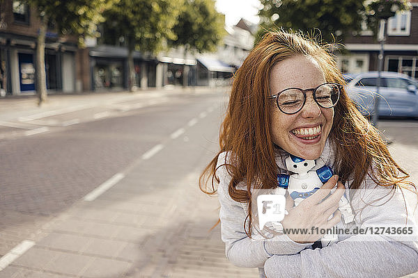 Redheaded woman hugging toy robot