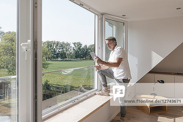 Mature man using tablet at the window in empty room