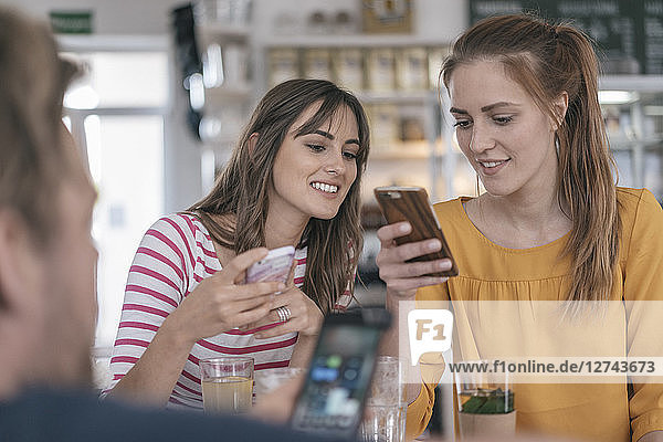Two girlfriends meeting in a coffee shop  using smartphones