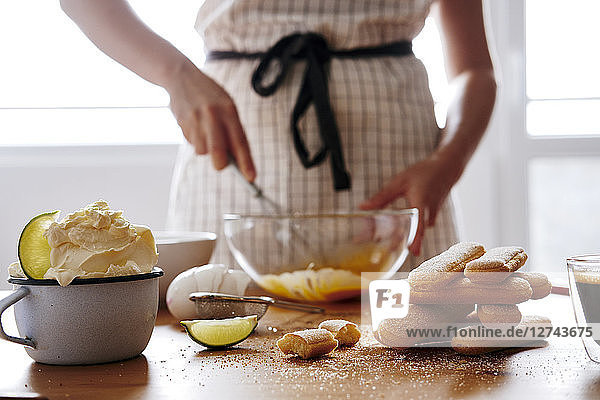 Stack of ladyfingers and cup of mascarpone on wooden table for preparing Tiramisu