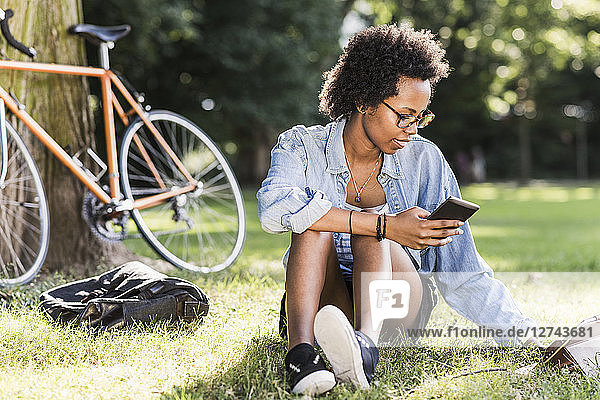 Young woman resting in park with cell phone and tablet