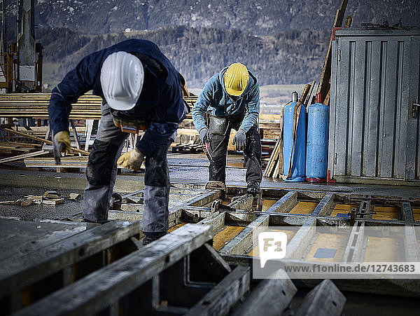 Construction workers working on plywood