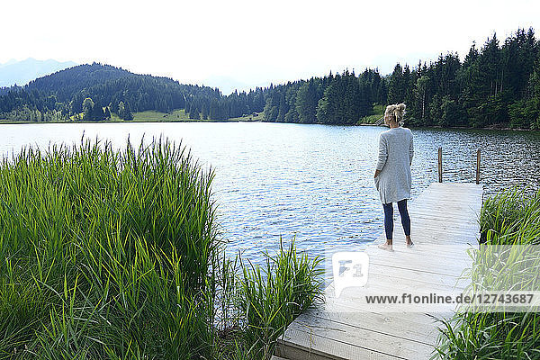 Germany  Mittenwald  woman standing on jetty at lake looking at distance