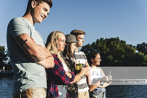 Group of friends standing at the water looking out