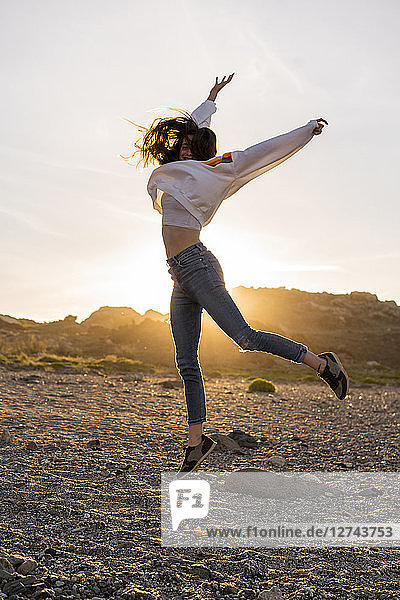 Young woman at the beach  dancing at sunset