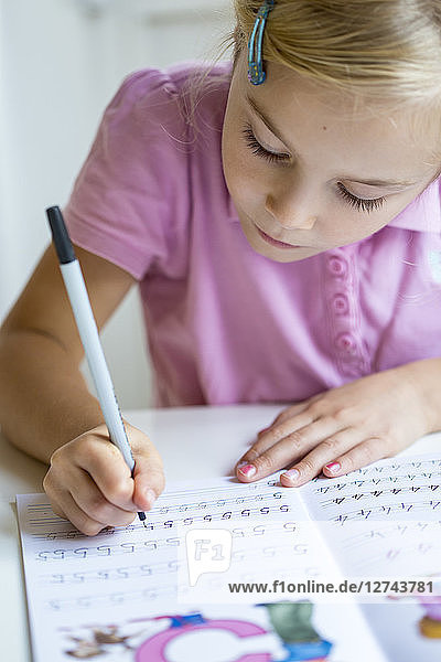 Little girl writing numbers in exercise book