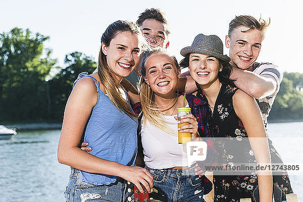 Portrait of group of happy friends at the riverside