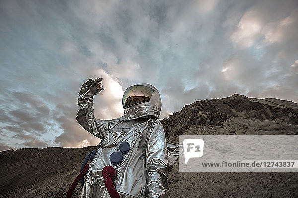 Spaceman on a nameless planet  taking rock samples