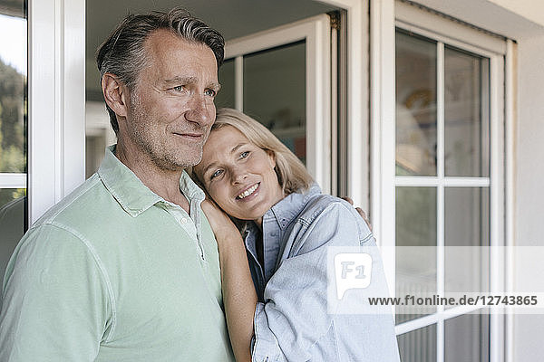 Portrait of smiling mature couple at French window