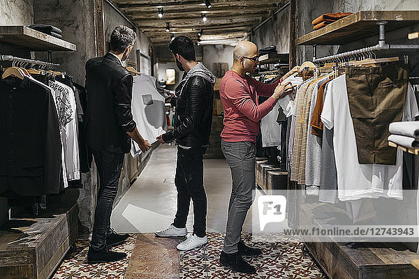 Three men in modern menswear shop with new collection