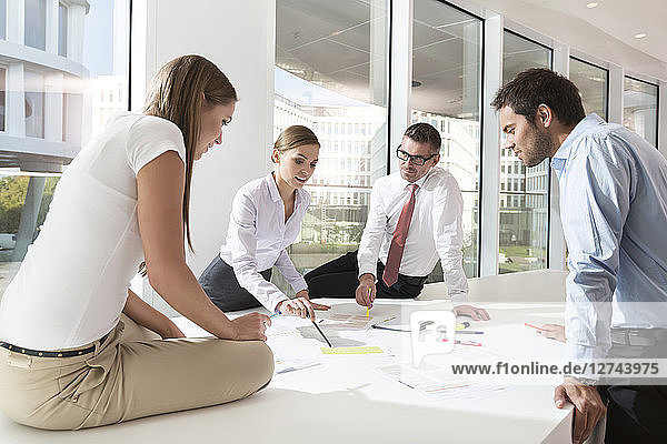Team of four business people having a meeting at conference table