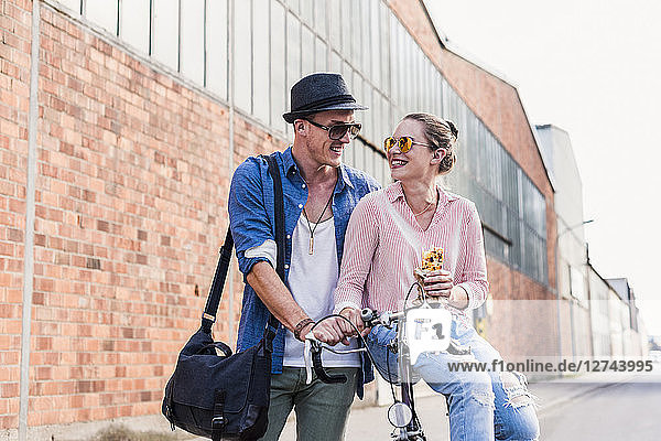 Young couple with bicycle on the street