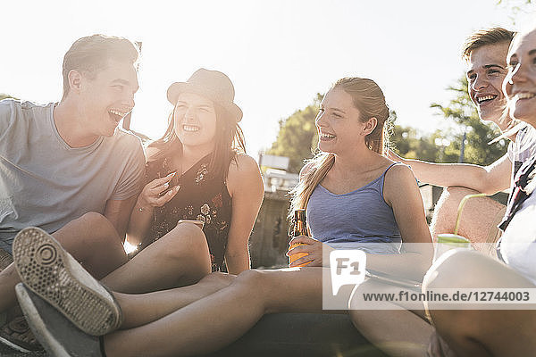 Group of happy friends sitting together outdoors