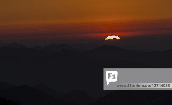Spain  Cantabria  setting sun behind mountains
