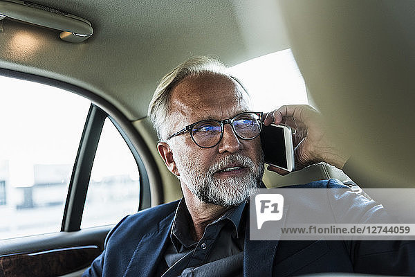 Mature businessman sitting on backseat in car  talking on the phone
