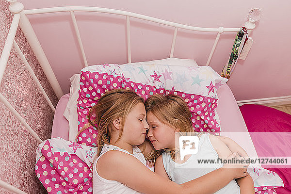 Two little sisters resting on bed