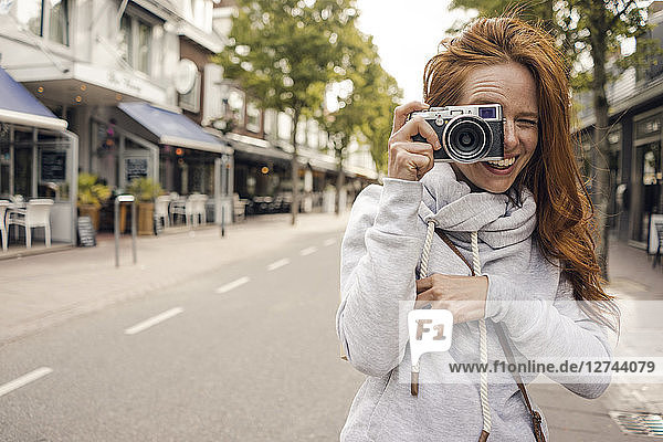 Redheaded woman using analogue camera