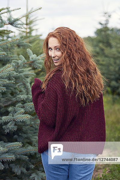 Portrait of smiling redheaded young woman in the woods
