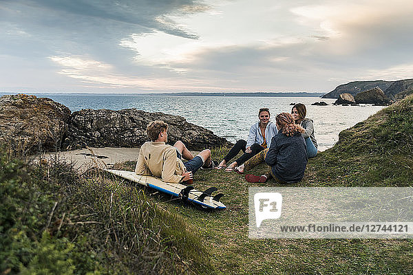 Happy friends with surfboard socializing at the coast at sunset