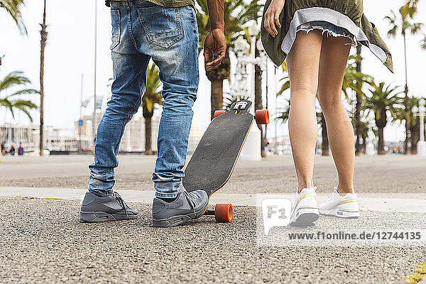 Spain  Barcelona  legs of multicultural young couple with longboard standing on promenade