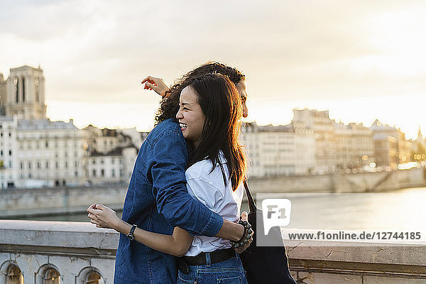France  Paris  happy young couple hugging at river Seine at sunset